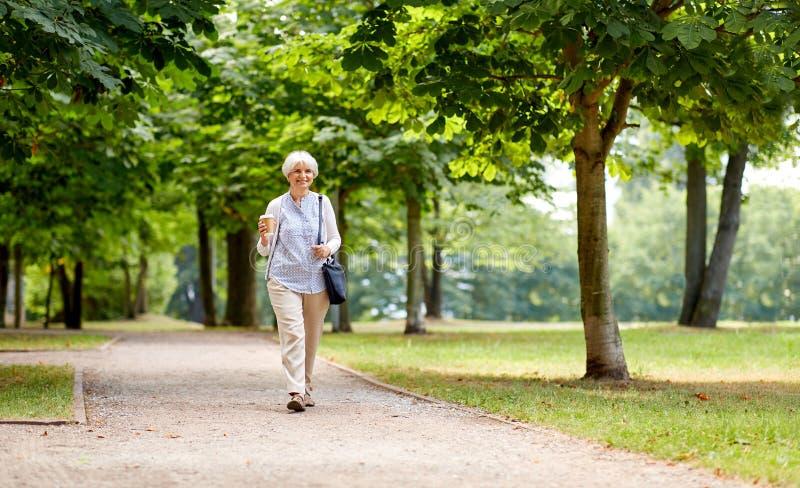 Hogere vrouw die met meeneemkoffie bij park lopen stock foto