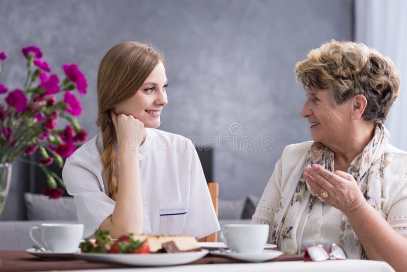 Hogere Vrouw die met Werker uit de hulpverlening spreken royalty-vrije stock afbeeldingen