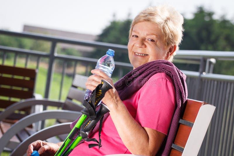 Hogere vrouw die na het noordse lopen, sportieve levensstijlen in oude dag rusten royalty-vrije stock afbeeldingen