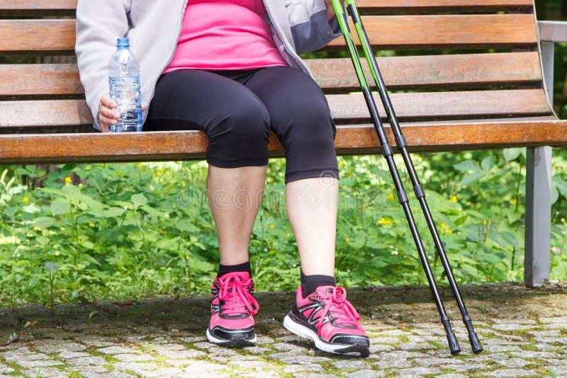 Hogere vrouw die na het noordse lopen, sportieve levensstijlen in oude dag rusten royalty-vrije stock afbeelding