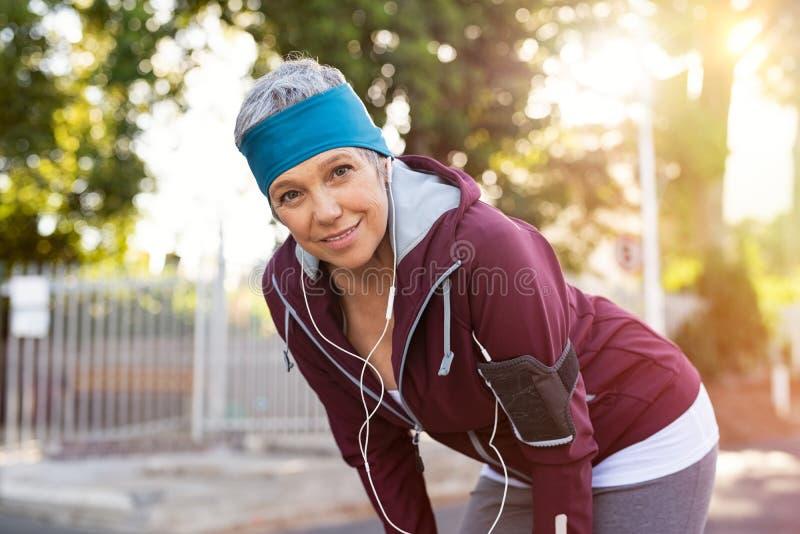 Hogere vrouw die na jogging rusten stock afbeelding