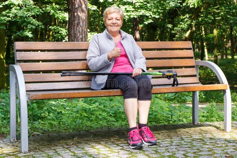 Hogere vrouw die na noordse lopende en tonende duimen omhoog rusten, sportieve levensstijlen royalty-vrije stock fotografie