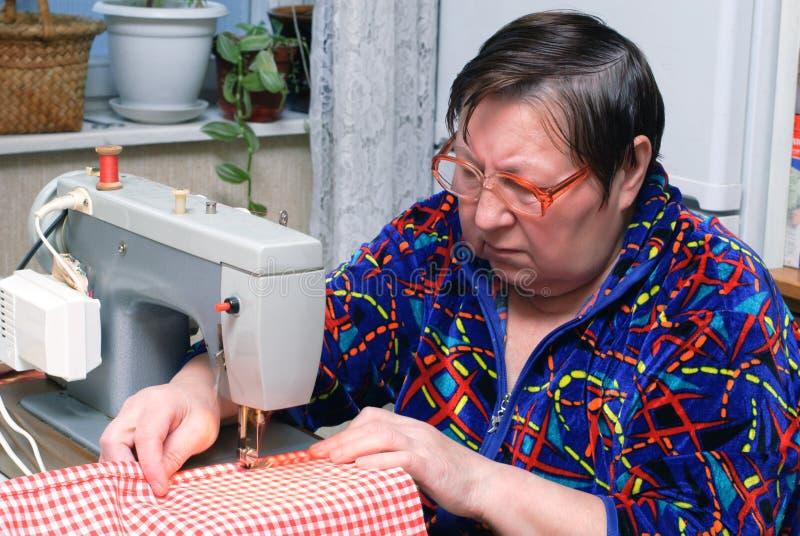 Hogere vrouw die naaimachine met behulp van royalty-vrije stock afbeeldingen