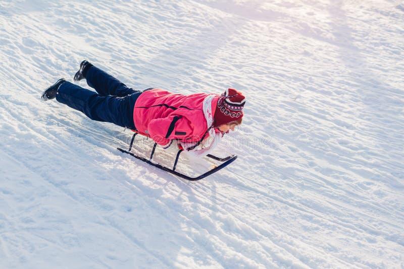 Hogere vrouw die neer sledding Vrouw die pret hebben die op ar in de winterpark liggen stock afbeeldingen
