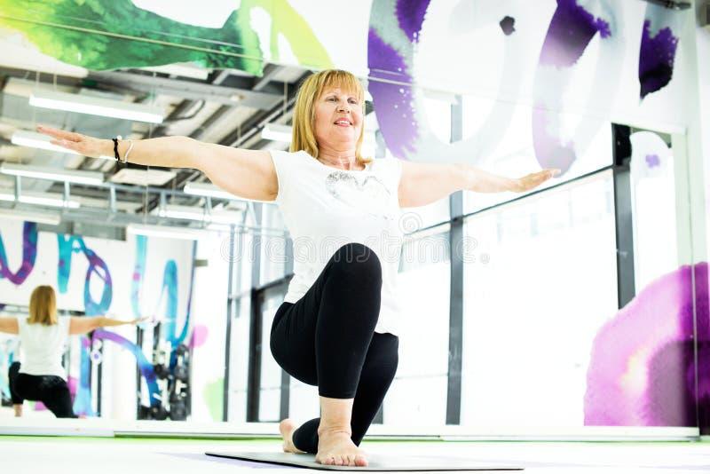 Hogere vrouw die oefening doen bij gymnastiek stock foto's