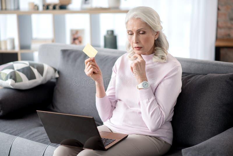 Hogere vrouw die online het winkelen in haar flat doen royalty-vrije stock afbeeldingen