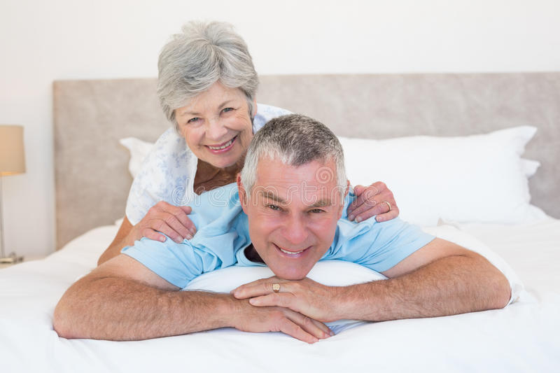 Hogere vrouw die op echtgenoot in slaapkamer liggen stock foto's