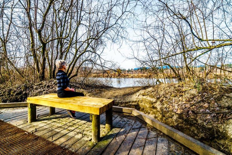 Hogere Vrouw die op een houten bank op de wandeling de sleep van Populierbar rusten aan Two-bit Bar in Glen Valley Regional Park royalty-vrije stock foto's