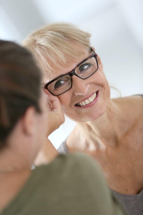 Hogere vrouw die op nieuwe oogglazen proberen stock fotografie