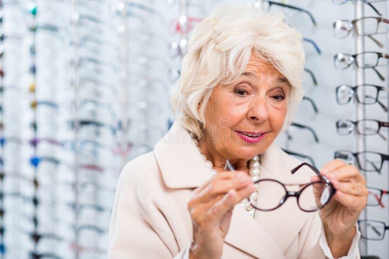 Hogere vrouw die op oogglazen proberen stock foto