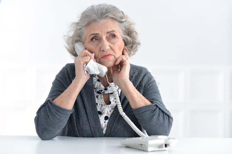 Hogere vrouw die op telefoon spreekt royalty-vrije stock fotografie