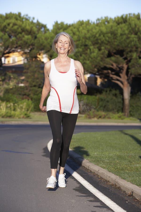 Hogere Vrouw die op Weg lopen stock fotografie
