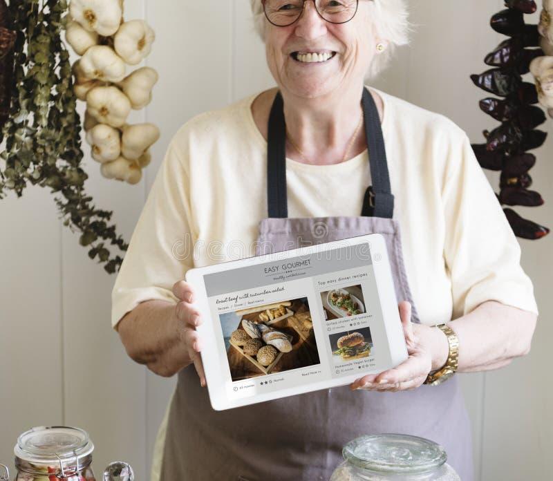 Hogere vrouw die organische gastronomische opbrengst verkopen bij delicatessenwinkel stock afbeeldingen