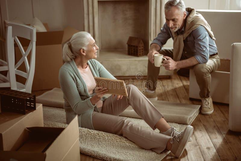 Hogere vrouw die oude foto tonen aan haar echtgenoot terwijl het nemen van onderbreking van de dozen van het verpakkingskarton royalty-vrije stock afbeelding