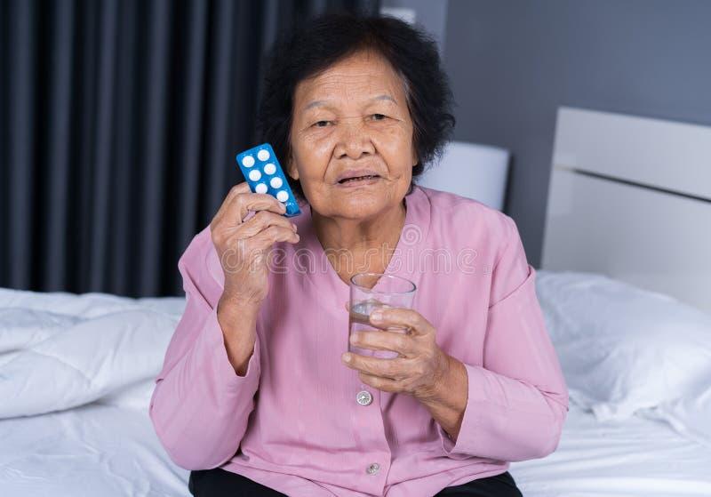 Hogere vrouw die pil met glas water in bed nemen stock afbeelding