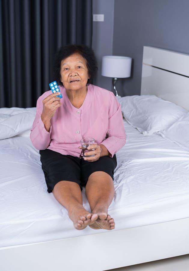 Hogere vrouw die pil met glas water in bed nemen stock foto