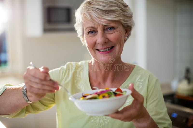 Hogere vrouw die plantaardige salade in kom houden royalty-vrije stock fotografie
