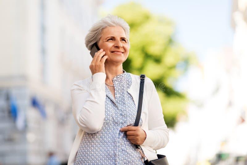 Hogere vrouw die smartphone in stad uitnodigen stock foto