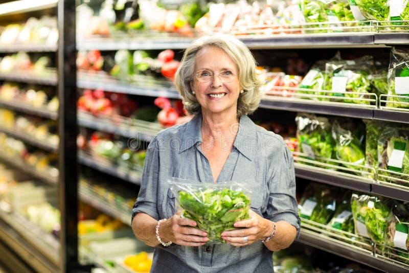 Hogere vrouw die sommige groenten uitkiezen stock fotografie