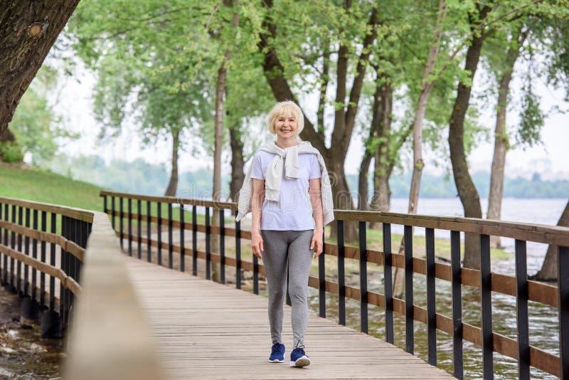 hogere vrouw die in sportkleding op houten weg lopen stock foto's