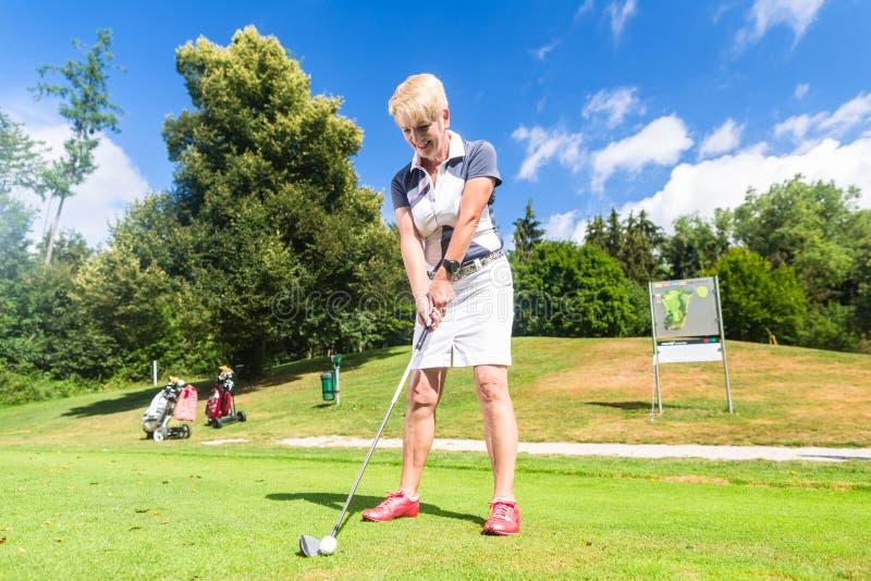 Hogere vrouw die T-stukslag op golfcursus doen royalty-vrije stock afbeelding