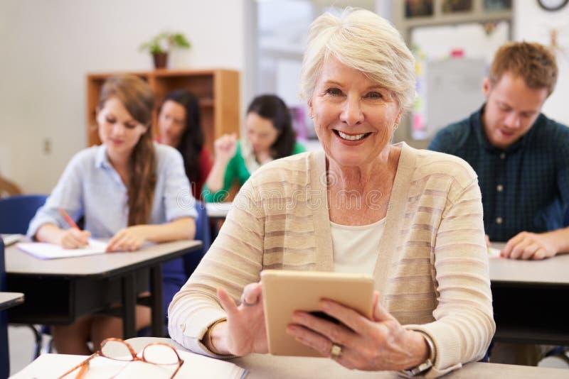 Hogere vrouw die tabletcomputer met behulp van bij volwassenenvormingsklasse royalty-vrije stock foto