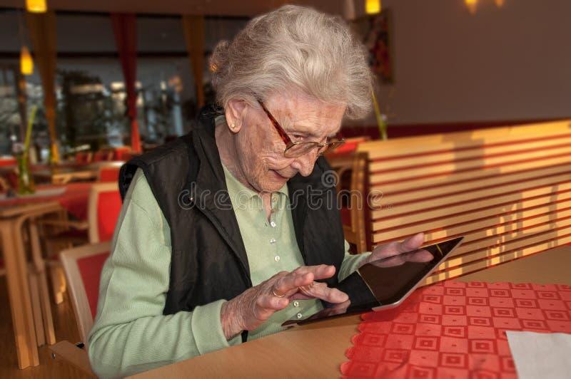 Hogere vrouw die tabletcomputer proberen te behandelen stock foto's