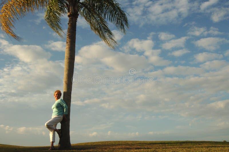 Hogere vrouw die tegen palm leunt royalty-vrije stock foto's