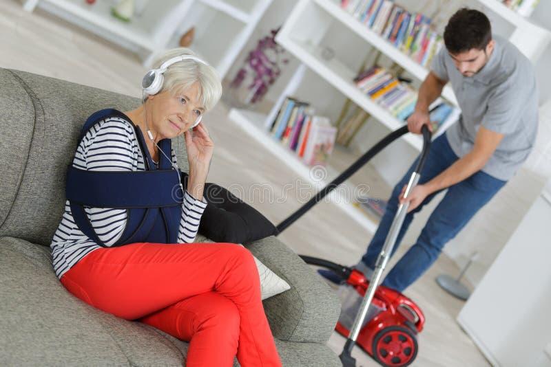 Hogere vrouw die terwijl jonge man schoonmakend huis ontspant stock foto's
