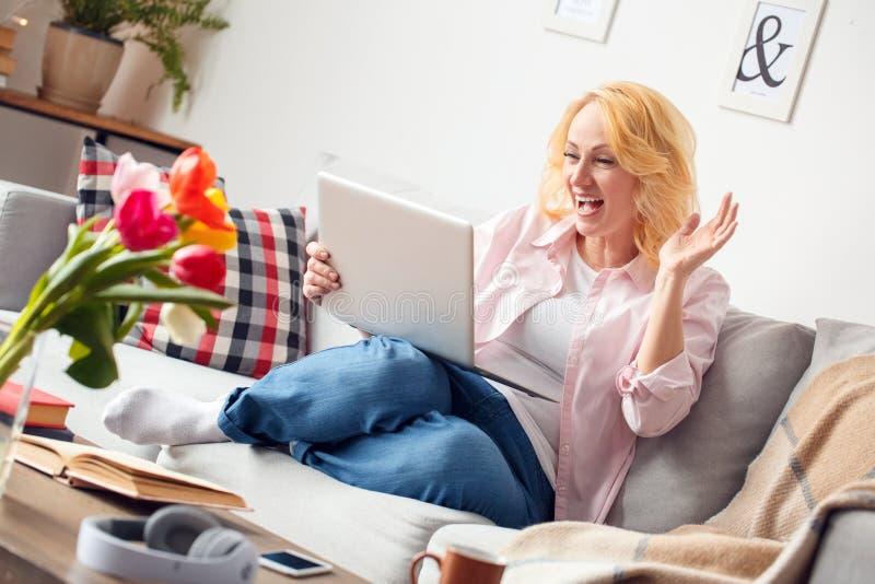 Hogere vrouw die thuis hebbend videogesprek bij laptop vrolijk glimlachen zitten stock foto's