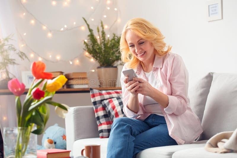 Hogere vrouw die thuis het doorbladeren blije smartphone zitten stock foto