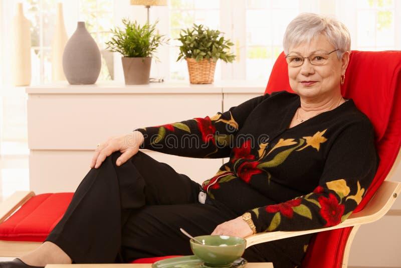 Hogere vrouw die thuis ontspant stock afbeelding