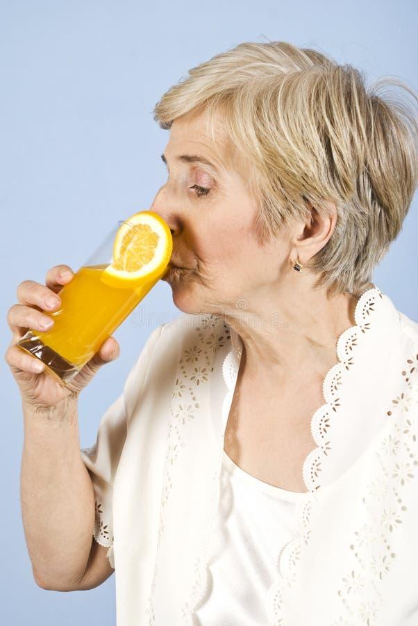 Hogere vrouw die vers jus d'orange drinkt stock foto