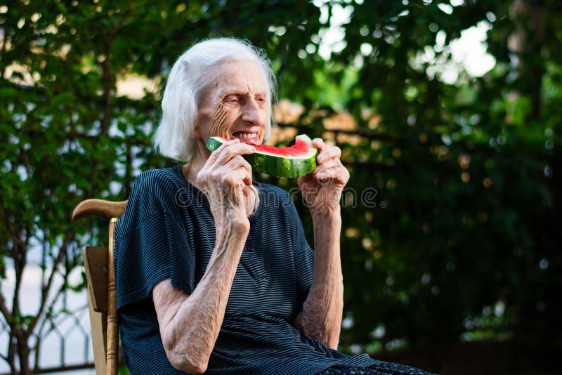 Hogere vrouw die watermeloen in openlucht eten royalty-vrije stock fotografie