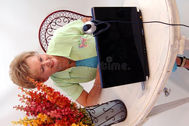 Hogere vrouw die webcam gebruikt stock afbeelding