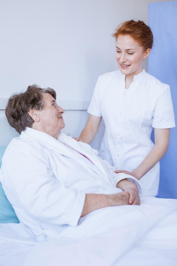 Hogere vrouw die in wit het ziekenhuisbed ligt met jonge nuttige verpleegster die haar hand houdt royalty-vrije stock foto
