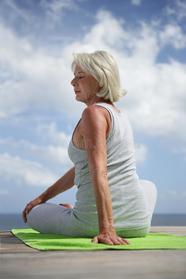 Hogere vrouw die yoga doet stock fotografie