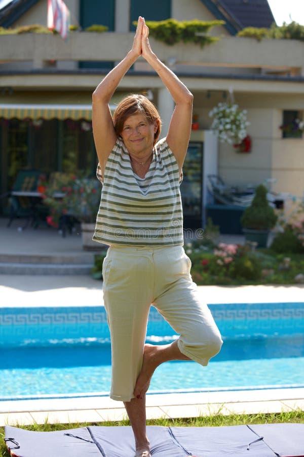 Hogere vrouw die yoga doet royalty-vrije stock afbeelding