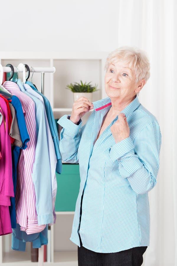 Hogere vrouw die zich omhoog kleden stock foto's