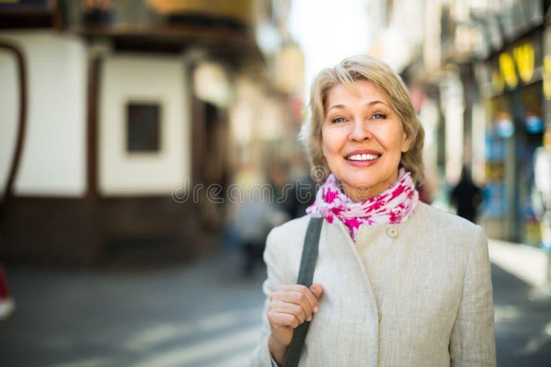 Hogere vrouw die zich op straat in stad bevinden stock fotografie