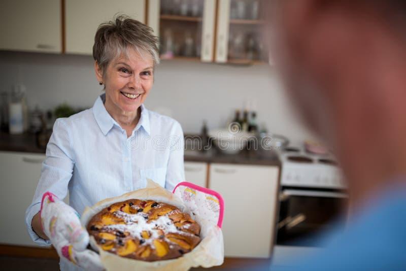 Hogere vrouw die zoet voedsel voorbereiden stock afbeelding