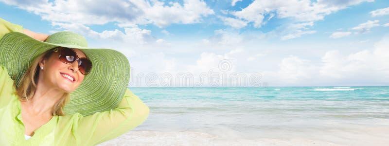 Hogere vrouw die zonnebril en een hoed dragen. stock foto