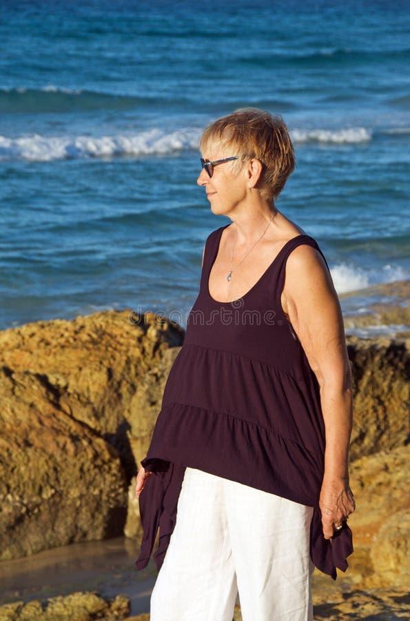 Hogere vrouw door het overzees royalty-vrije stock foto