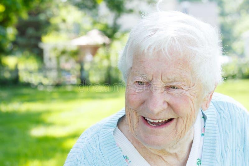 Hogere vrouw in een blauwe sweater buiten royalty-vrije stock afbeelding