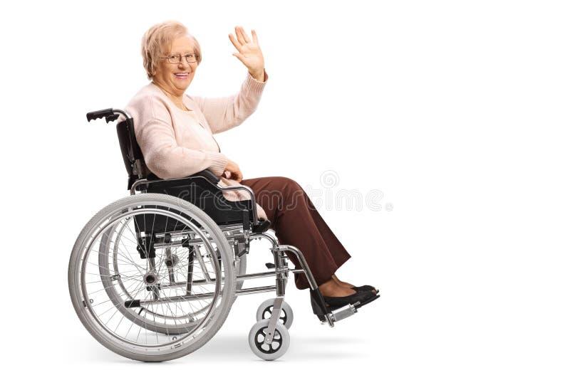 Hogere vrouw in een rolstoel die bij de camera en het golven glimlachen royalty-vrije stock fotografie