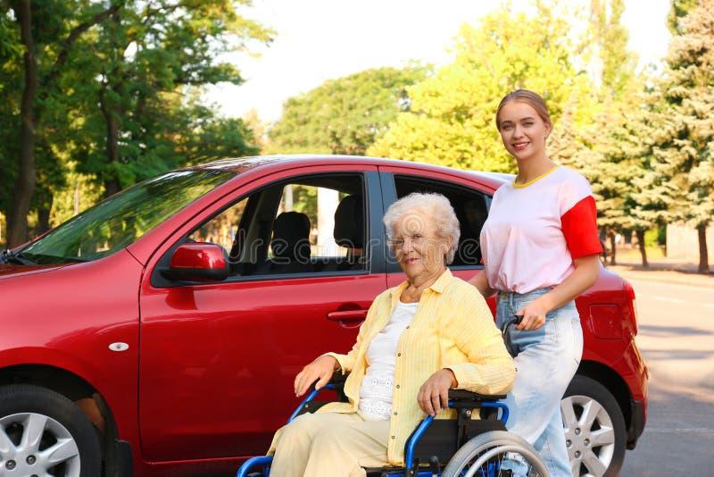 Hogere vrouw in een rolstoel met kleindochter in de buurt van de auto stock foto's