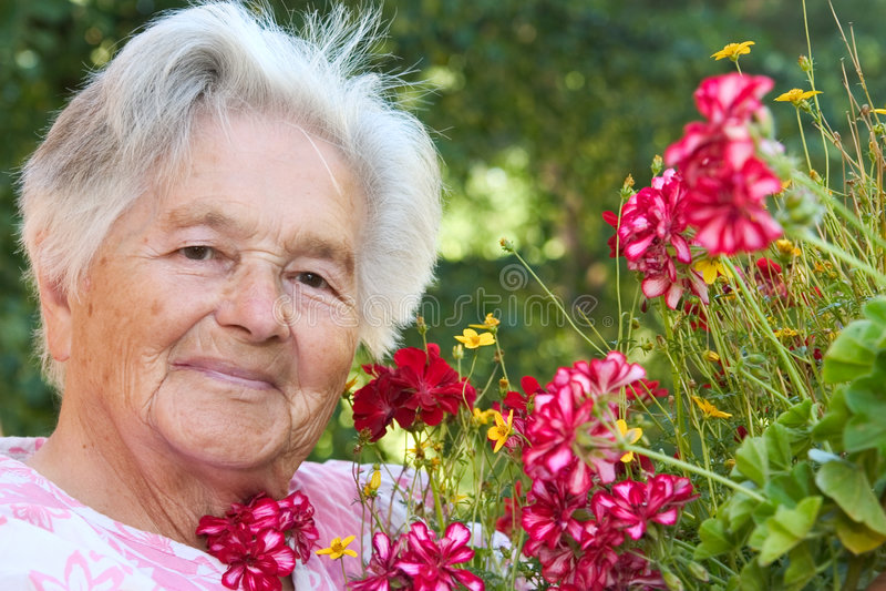 Hogere vrouw en bloemen royalty-vrije stock afbeelding