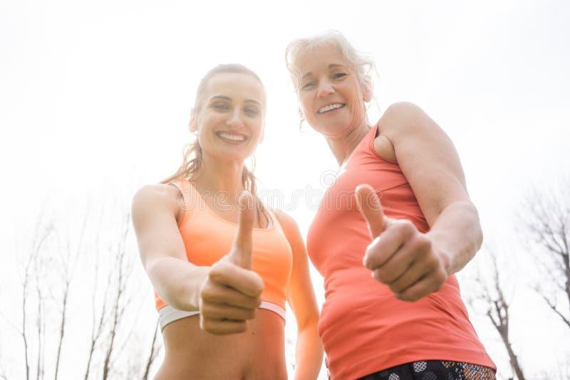 Hogere vrouw en dochter die duimen voor sport opgeven stock foto