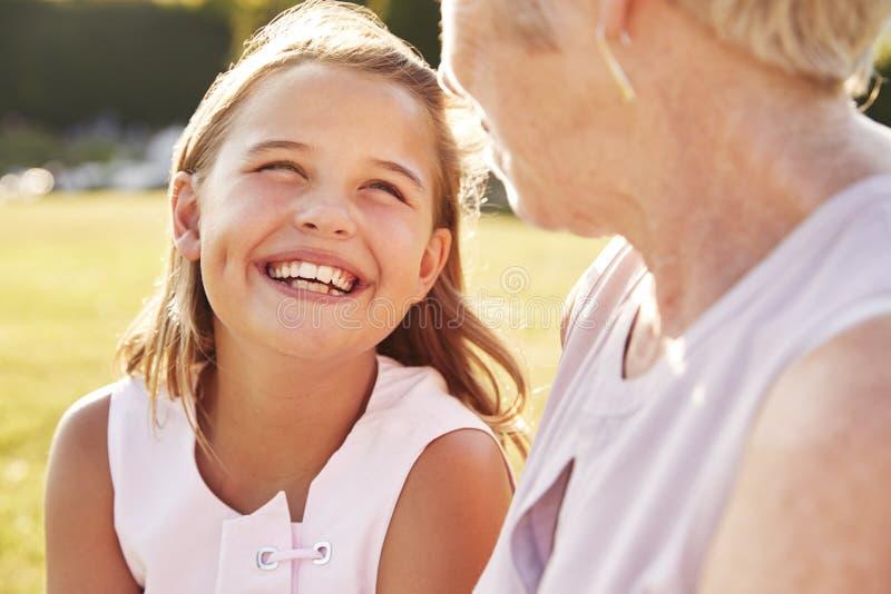 Hogere vrouw en kleindochter die elkaar bekijken royalty-vrije stock fotografie