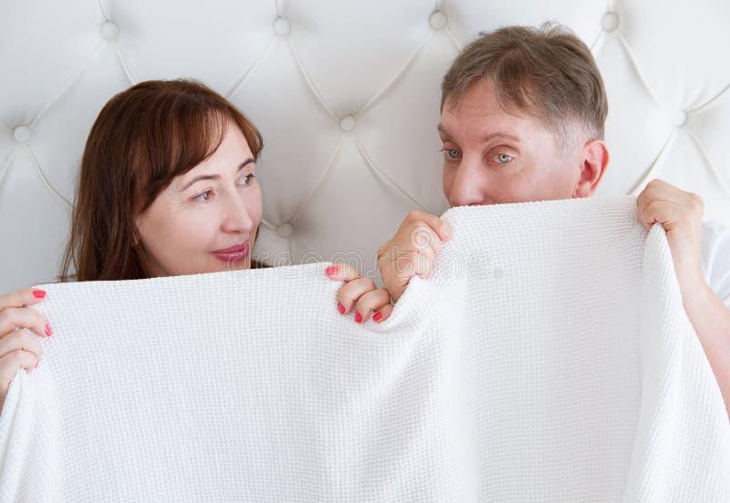 Hogere Vrouw en man in bed Middenleeftijdspaar die in slaapkamer liggen en onder malplaatje lege witte deken verbergen De ruimte  royalty-vrije stock foto